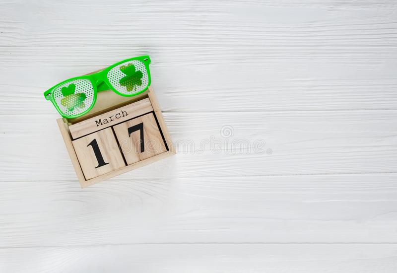Creative festive St Patricks background with wooden calendar and glasses with shamrock on white wooden table. Flat lay. Copy space royalty free stock photo