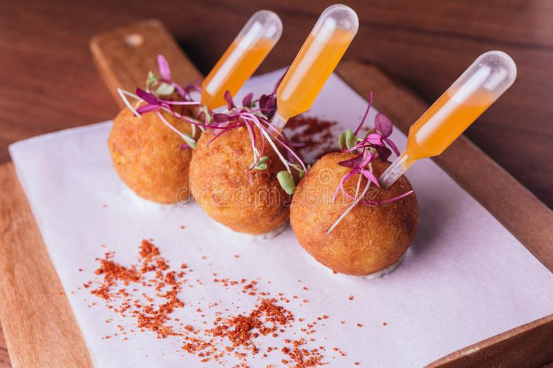 Creative fine dining: Chicken Biryani Arancini served in rice ball with sweet and spicy dip on wooden chop board.  royalty free stock photo