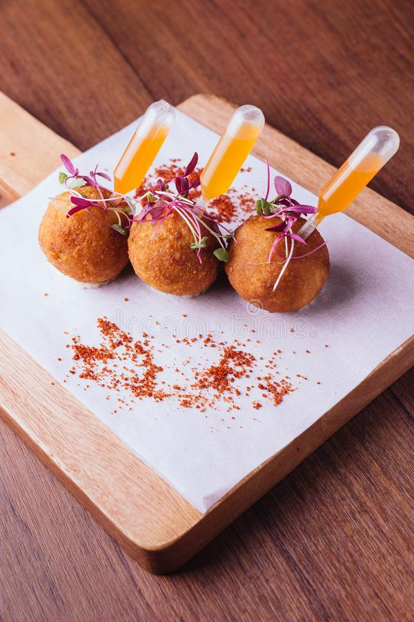 Creative fine dining: Chicken Biryani Arancini served in rice ball with sweet and spicy dip on wooden chop board.  royalty free stock photography