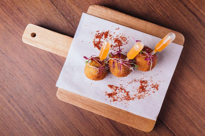 Creative fine dining: Chicken Biryani Srancini served in rice ball with sweet and spicy dip on wooden chop board.  royalty free stock images