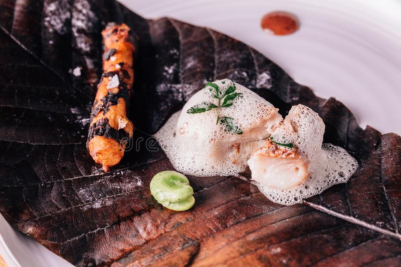 Creative Fine Dining: Fish topping with culinary foam serves with pea and grilled root with salt on torched leaf.  royalty free stock images