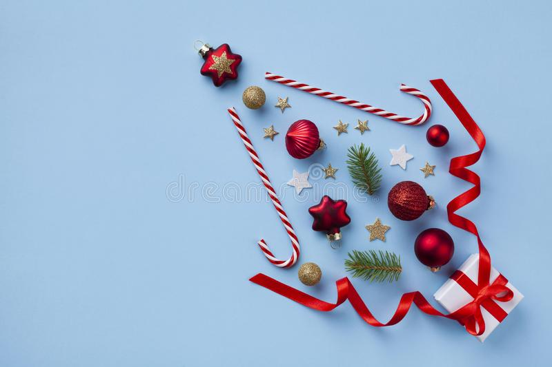 Creative fir tree made of gift box, Christmas tree ornaments and holiday decorations on blue background top view. Flat lay. Creative fir tree made of gift box royalty free stock photography