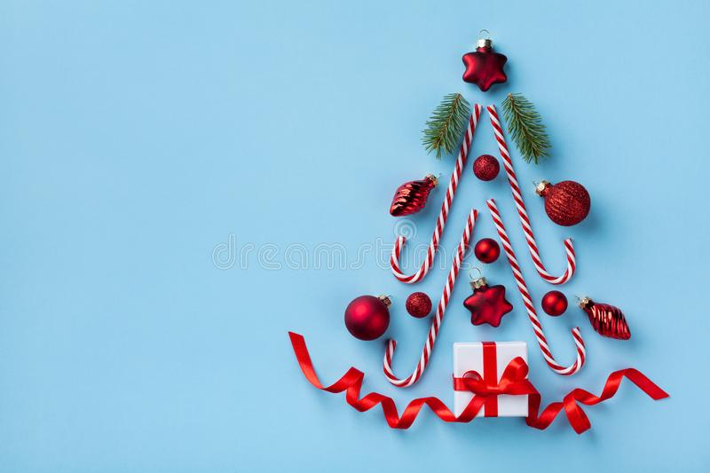Creative fir tree made of gift box, Christmas tree ornaments and holiday decorations on blue background top view. Flat lay royalty free stock photography
