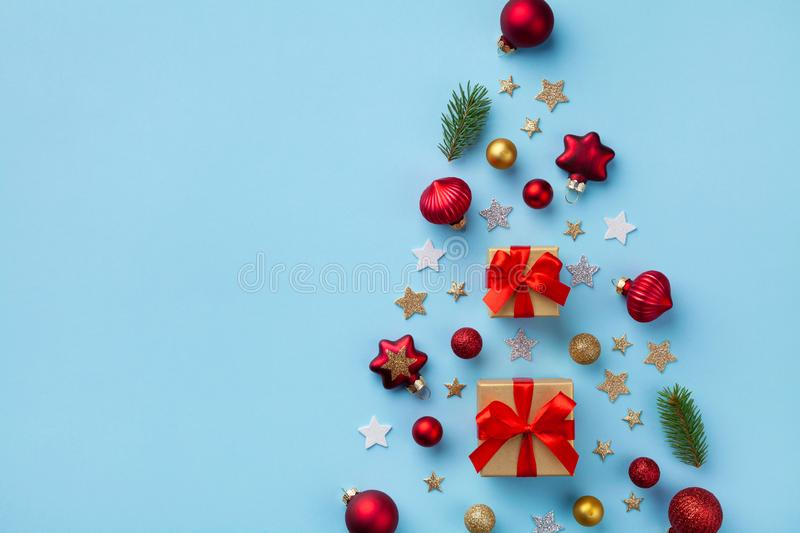 Creative fir tree made of gift box, Christmas tree ornaments and holiday decorations on blue background top view. Flat lay. Creative fir tree made of gift box stock photos