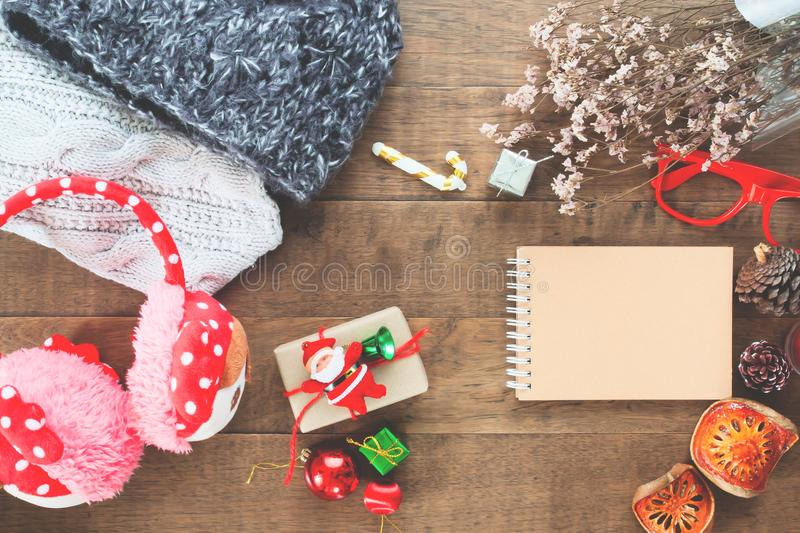 Creative flat lay of Christmas ornaments, winter accessories and craft notebook on wood background royalty free stock photos