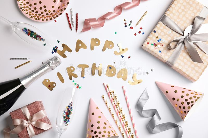 Creative flat lay composition with bottle of champagne, party accessories and words HAPPY BIRTHDAY stock photos