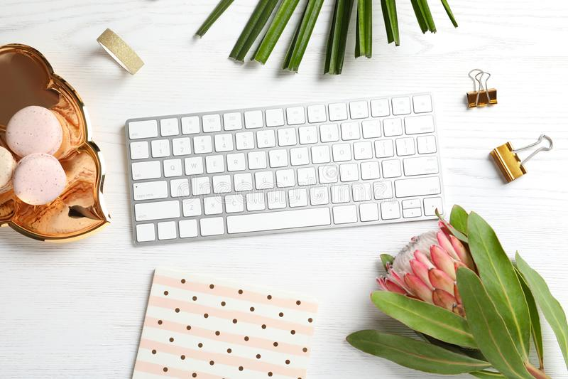 Creative flat lay composition with tropical flower, macaroons and computer keyboard stock photography