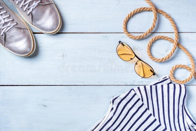 Creative flat lay concept of summer travel vacations. Top view of shiny sneakers, sunglasses and rope on pastel blue background wi royalty free stock photography