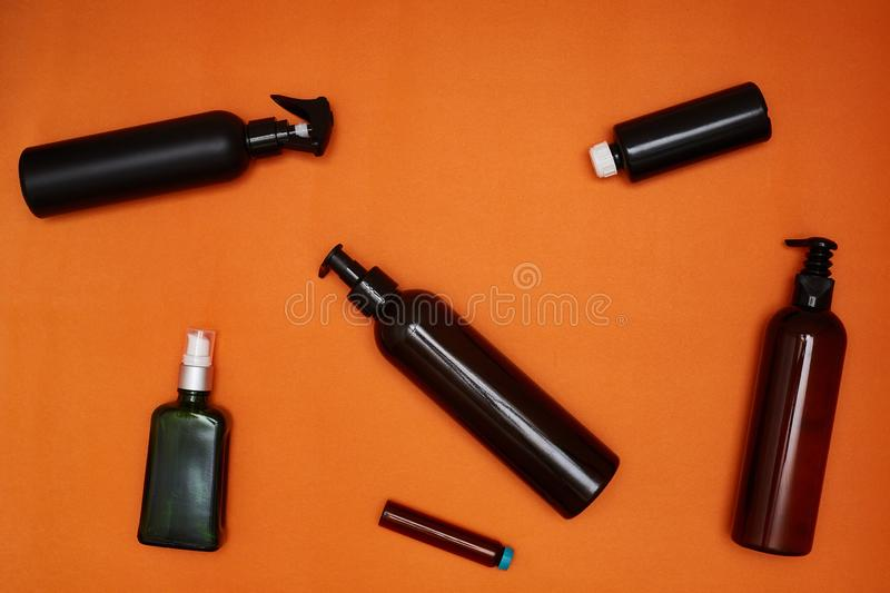 Creative flat lay of dark cosmetic bottles on a bright orange background. Beauty blogger concept. Top view.  stock photography