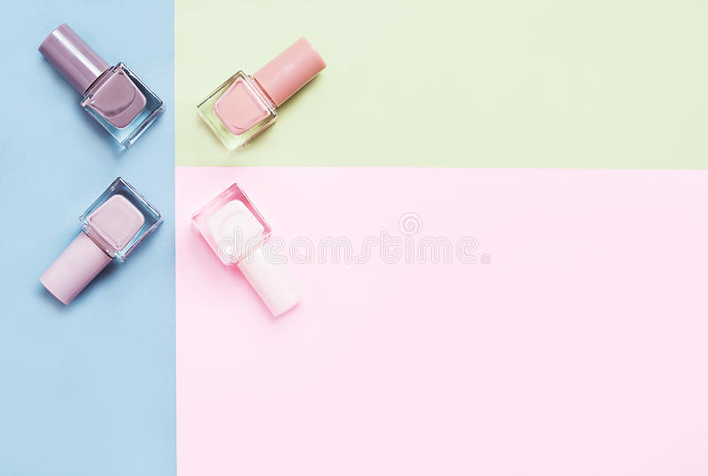 Creative flat lay of fashion bright nail polishes on a colorful background. Minimal style. Copy space. Beauty blogger stock photo