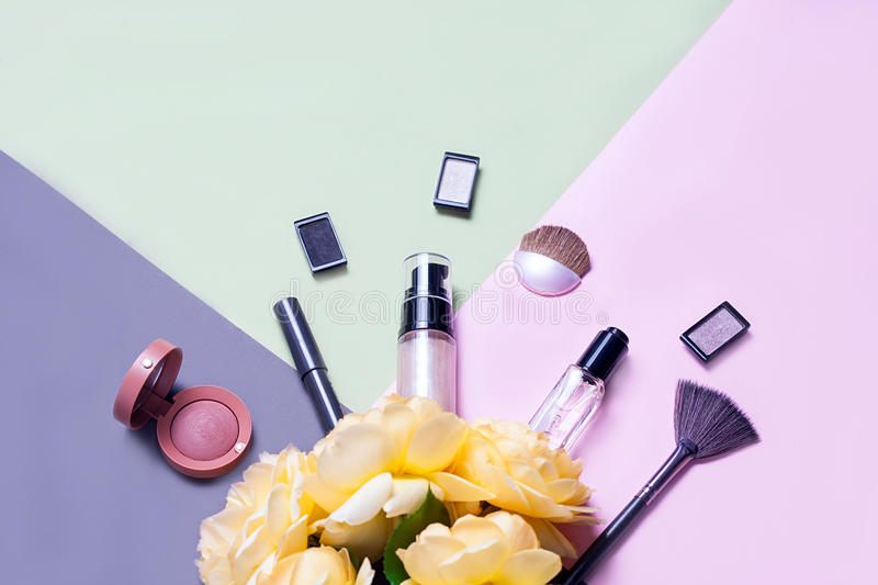 Creative flat lay of fashion bright nail polishes and decorative cosmetic on a colorful background with yellow roses stock photos