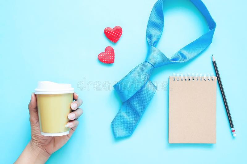 Creative flat lay of Father`s Day concept. Necktie, notebook and woman hand holding coffee cup on pastel colour royalty free stock photography