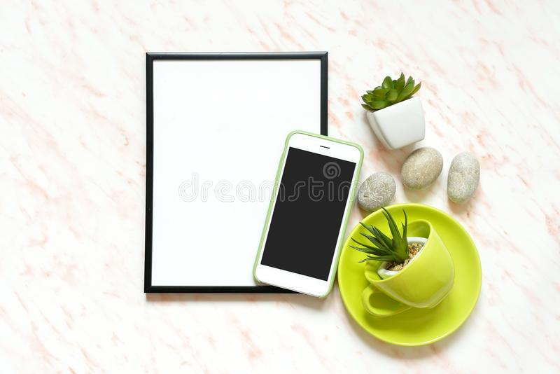 Creative Flat lay marble desk with white empty frame for text, phone, cup, stones and succulents background royalty free stock photo
