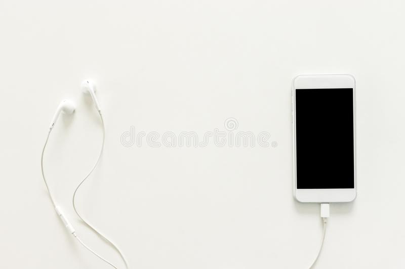 Creative flat lay photo of workspace desk with earphones and mobile phone with blank screen on copy space white background. stock image