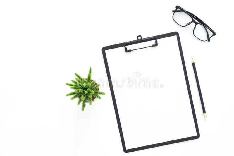 Top view office desk with glasses, pencil, blank clipboard and plant on white color background. royalty free stock photo