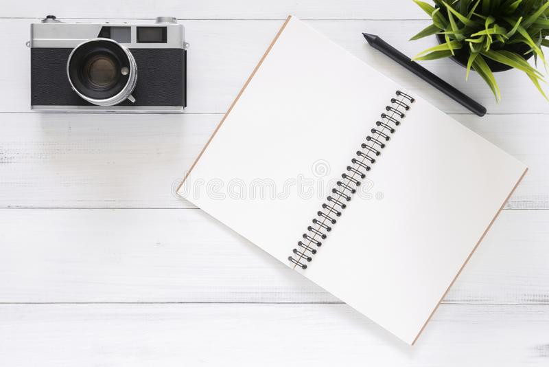 Creative flat lay photo of workspace desk. White office desk wooden table background with mock up notebooks and retro camera. Minimal work space - Creative flat stock photo