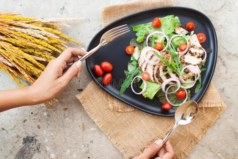 Creative flat lay of salad with grilled chicken, onions and tomatoes on black plate with woman`s hands royalty free stock photos