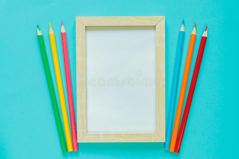 Creative flat lay with school suppllies. Mock up frame and multicolored pencils on blue background. Back to school.  stock images