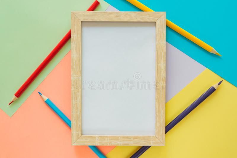 Creative flat lay with school suppllies. Mock up frame and multicolored pencils on pastel colorful background. Back to school stock image