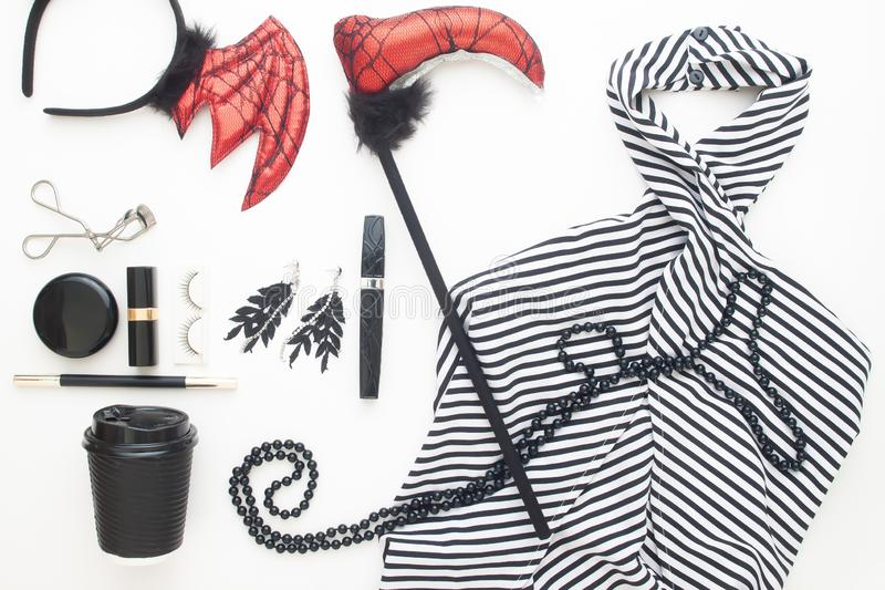 Creative flat lay of woman dress and accessories for Halloween party on white background royalty free stock photos