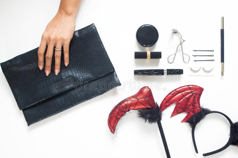 Creative flat lay of woman hand holding trendy purse with Halloween party accessories and cosmetics on white background. stock images