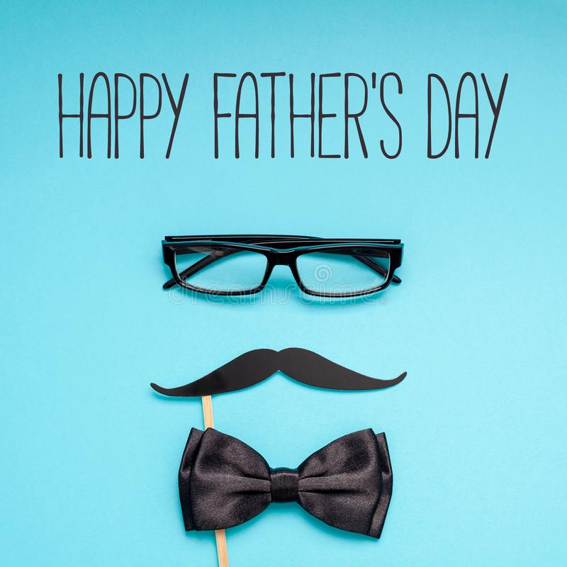 Happy fathers day postcard with moustache glasses. Creative flatlay overhead top view retro black paper photo booth props moustaches blue background copy space royalty free stock image