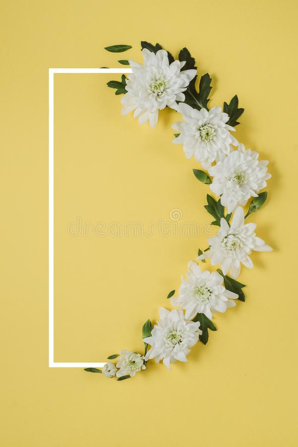 Creative flowers composition. Wreath made of white flowers on yellow background with a drawn frame. Mothers day, womens day, royalty free stock photos