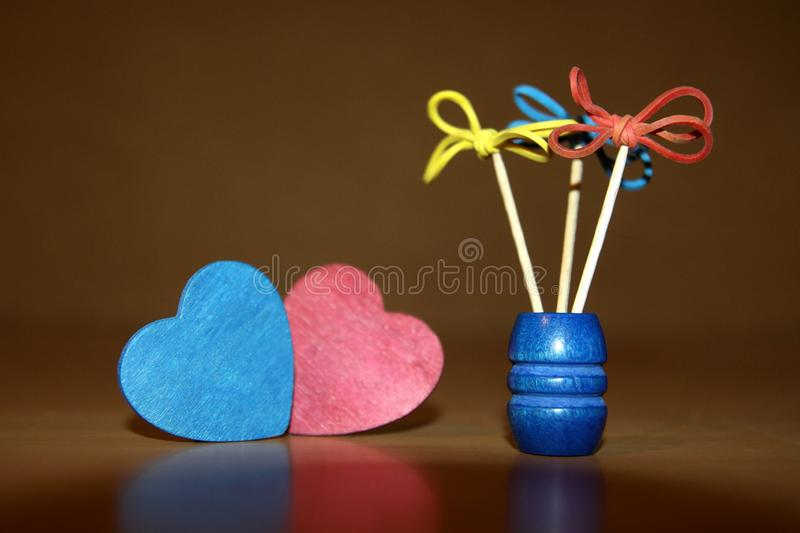 Creative flowers of gum and toothpicks red and blue wooden heart shaped hearts.  royalty free stock photography