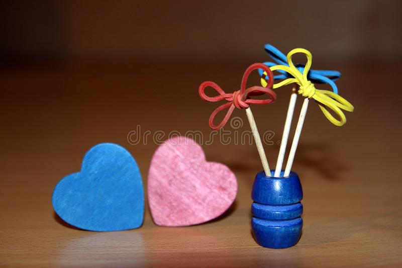 Creative flowers made of gum and toothpicks red and blue wooden hearts in the shape of a heart.  stock photo