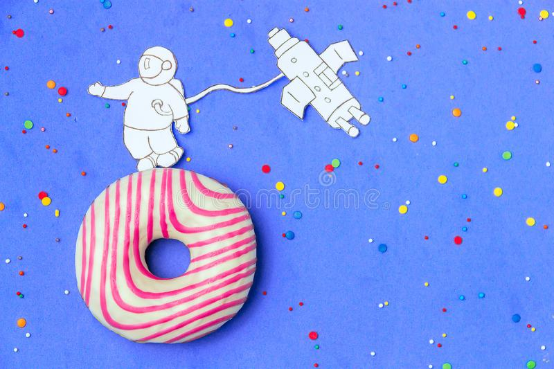 Creative Food Minimalism, Donut in Shape of Planet in Blue Sky with Astronaut, Space Ship Top View, Copy Space. royalty free stock images
