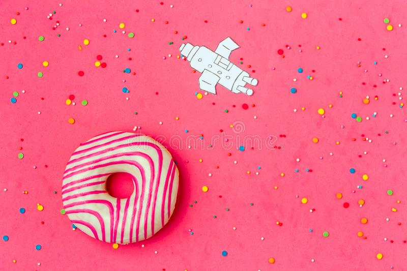 Creative Food Minimalism, Donut in Shape of Planet in Pink Sky with Space Ship Top View, Copy Space. stock photo