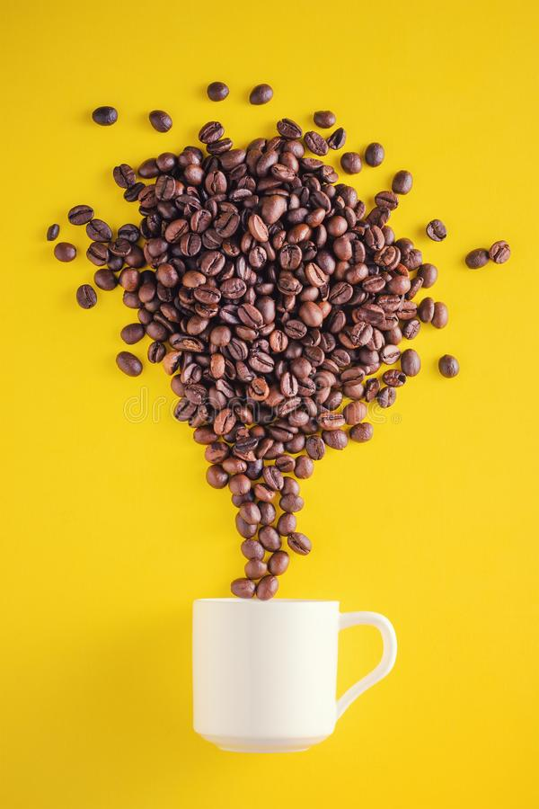 Creative food photo. Coffee beans exploding with fireworks from a cup on a yellow background stock photography