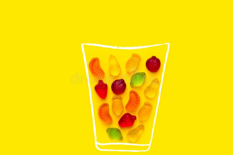 Creative food poster banner card template. Hand drawn chalk glass with fresh fruits juice imitated by gummy jelly candies. On yellow background. Summer vitamins royalty free stock photos