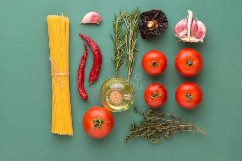 Creative food poster with flat lay knolling of Italian arrabiata pasta ingredients. Spaghetti tomatoes hot chili peppers herbs oil. Creative food poster with stock image