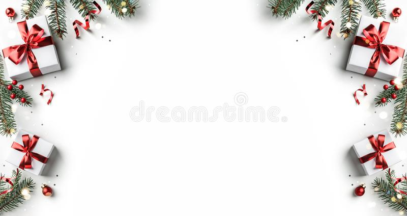 Creative frame made of Christmas fir branches, gift boxes, red decoration, sparkles and confetti on white background. Xmas and New. Year holiday, bokeh, light royalty free stock photography