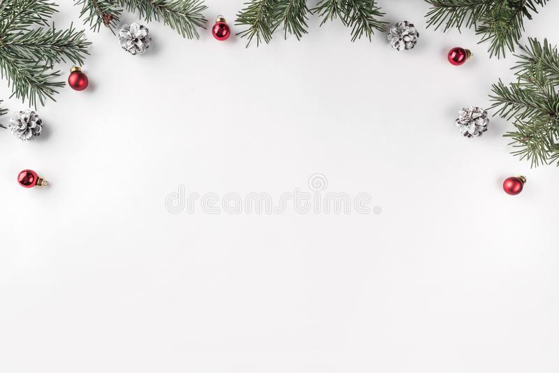 Creative frame made of Christmas fir branches on white background with red decoration, pine cones. royalty free stock image