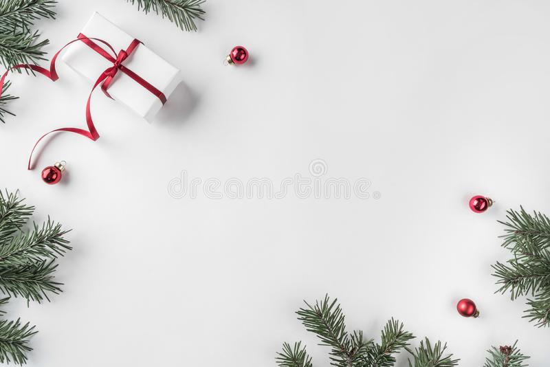 Creative frame made of Christmas fir branches on white wooden background with red decoration, pine cones royalty free stock image