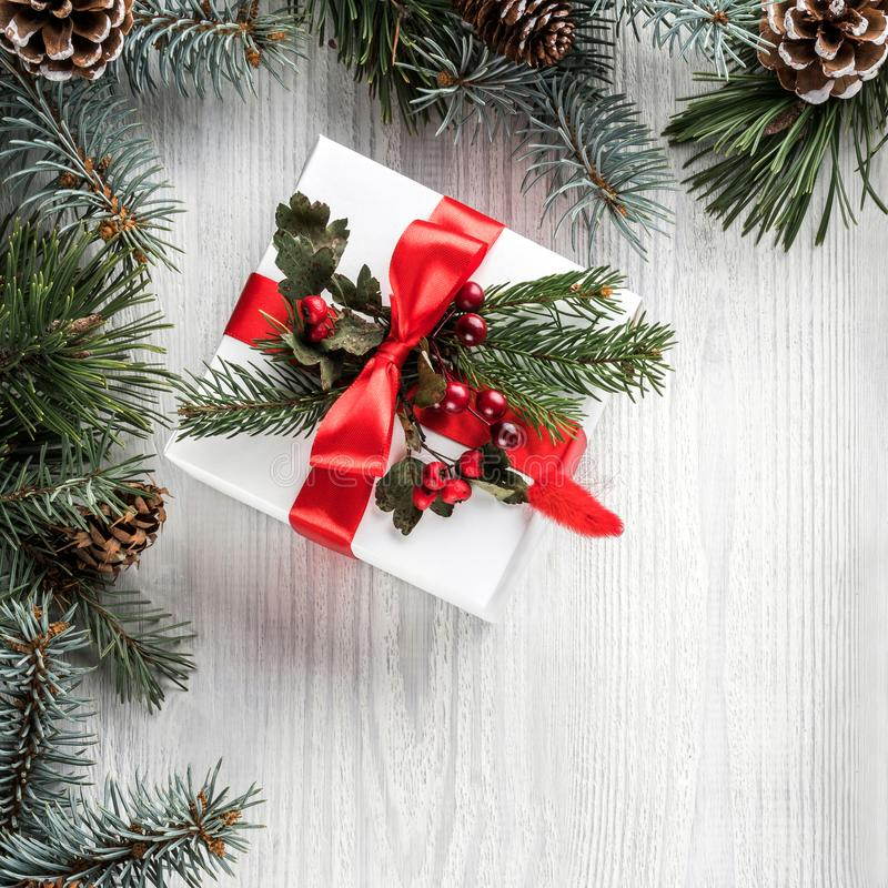 Creative frame made of Christmas fir branches on white wooden background with gift box, pine cones. Xmas and New Year theme. royalty free stock photos