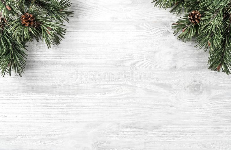 Creative frame made of Christmas fir branches on white wooden background with pine cones. Xmas and New Year theme. royalty free stock image