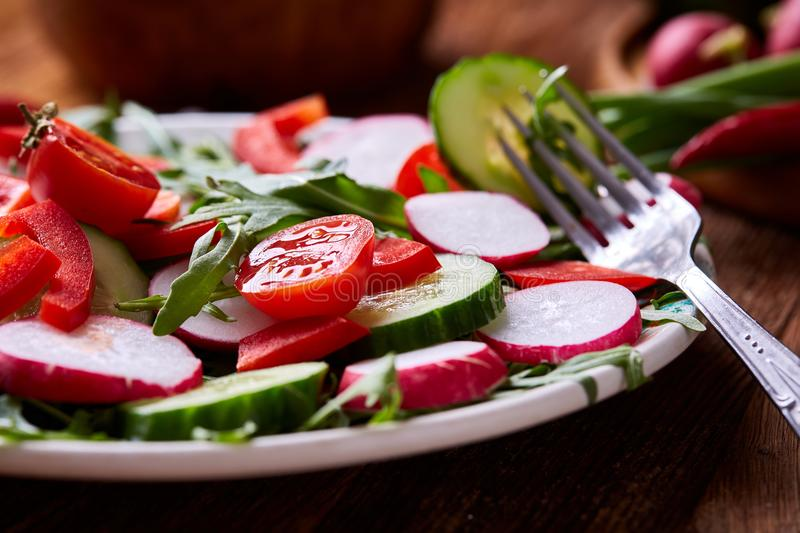Creative fresh vegetable salad with ruccola, cucumber, tomatoes and raddish on white plate, selective focus royalty free stock photo