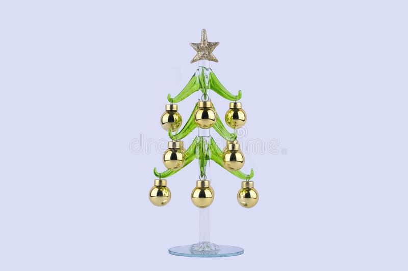 Creative glass christmas tree with yellow balls and star on a light background. stock image