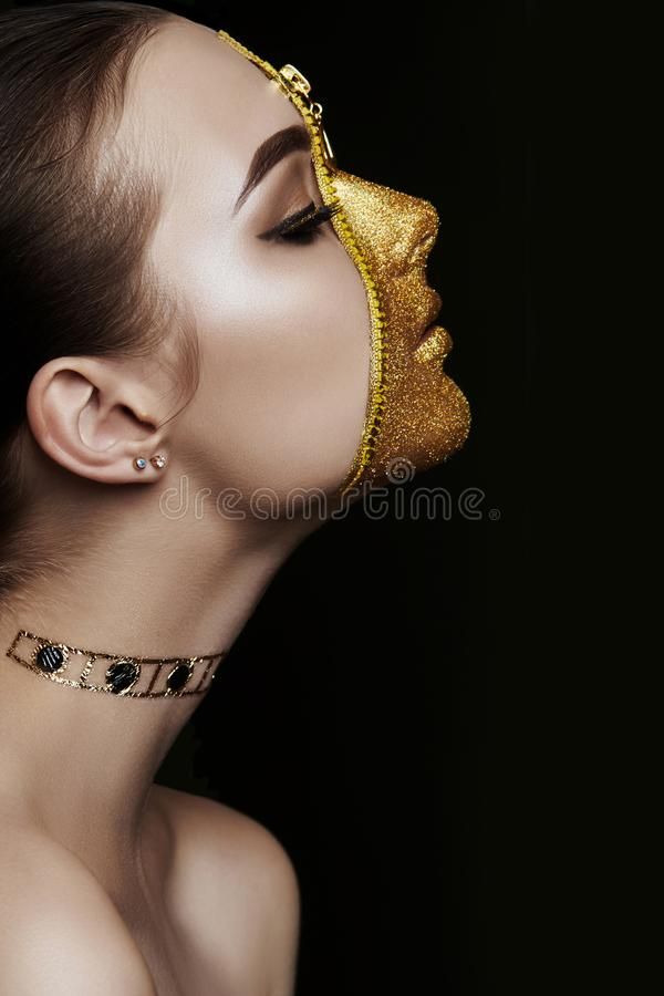 Creative grim makeup face of girl Golden color zipper clothing on skin. Fashion beauty creative cosmetics and skin care halloween royalty free stock image