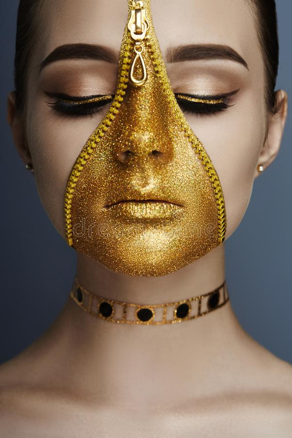 Creative grim makeup face of girl Golden color zipper clothing on skin. Fashion beauty creative cosmetics and skin care halloween. Brunette woman on dark royalty free stock images