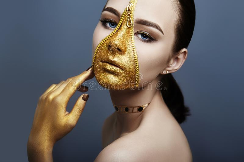 Creative grim makeup face of girl Golden color zipper clothing on skin. Fashion beauty creative cosmetics and skin care halloween stock photo