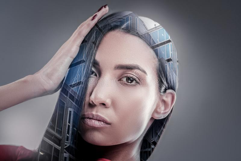 Pretty female person touching her hair. Creative haircut. Professional model looking straight at camera and pressing lips while raising her hand royalty free stock image