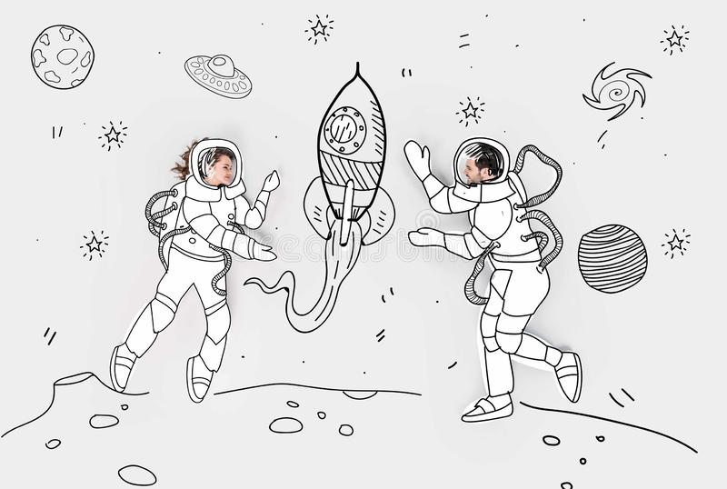 Creative hand drawn collage with couple in space suits. And rocket stock illustration