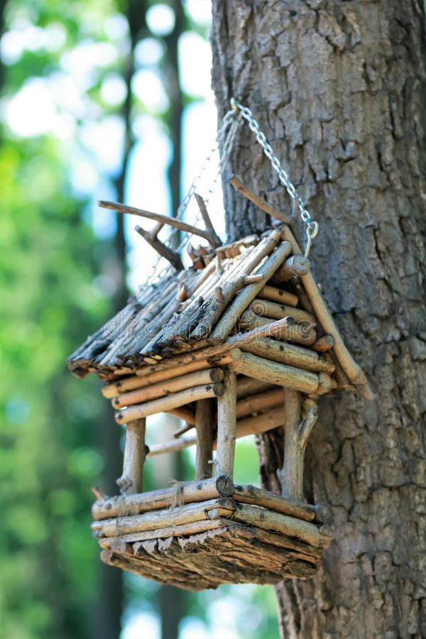 Creative hand made wooden bird house/bird feeder hanging on a chain on the tree in a park. DIY, creative hand made wooden bird house/bird feeder hanging on a stock image