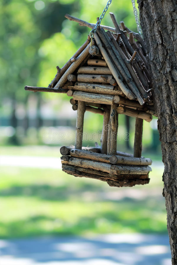 Creative hand made wooden bird house/bird feeder hanging on a chain on the tree in a park. DIY, creative hand made wooden bird house/bird feeder hanging on a royalty free stock photography