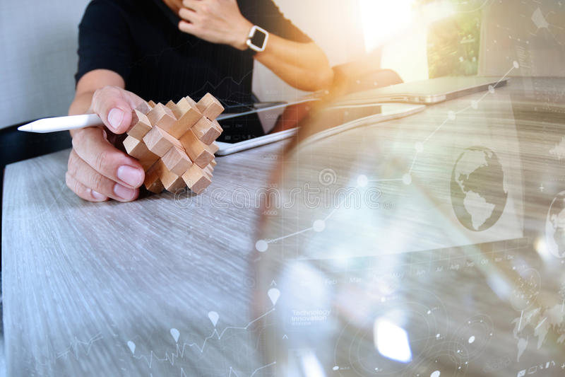 Creative hand showing wood puzzle and light bulb with laptop com. Puter and tablet computer as design concept royalty free stock images
