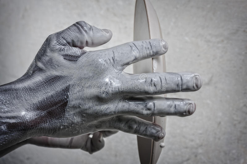 Creative hands. Wet black hands holding a ceramic plate ready for glazing stock photos
